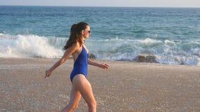 Ung kvinna i baddräkten som kör på havsstranden r Kvinnlig turist som har roligt Begrepp av arkivfilmer