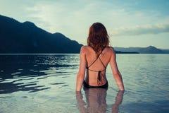 Ung kvinna i baddräktsammanträde på den tropiska stranden Fotografering för Bildbyråer
