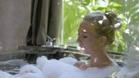 Ung kvinna i badkar lager videofilmer