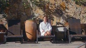 Ung kvinna i badrock som kopplar av på sunbed utomhus lager videofilmer