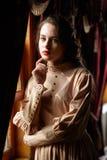 Ung kvinna i beige tappningklänning av tidigt - århundradestandinen för th 20 Arkivbilder