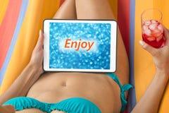 Ung kvinna i bikini på en hängmatta med minnestavlaapparaten som ser suddig blå bakgrund med ord & x22; Enjoy& x22; skriftligt på arkivbilder