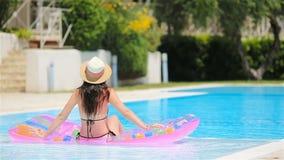 Ung kvinna i bikiniluftmadrass i den stora simbassängen lager videofilmer