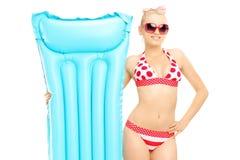 Ung kvinna i bikinin som rymmer en simningmadrass Arkivbilder