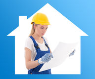 Ung kvinna i blå byggmästarelikformig med byggnadsplan Arkivbild