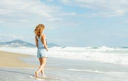 Ung kvinna i blå grov bomullstvilljumpsuit som promenerar stranden, och det stormiga havet på solig dag Arkivbilder