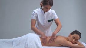 Ung kvinna i brunnsort Traditionella läka terapi- och masserabehandlingar Hälsa och hudomsorg, massage och rekreation arkivfilmer