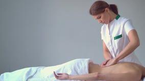 Ung kvinna i brunnsort Traditionella l?ka terapi- och masserabehandlingar H?lsa hudomsorg, massage, osteopathy och arkivfilmer