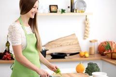 Ung kvinna i den gröna förklädematlagningen i köket Hemmafru som skivar ny sallad royaltyfria bilder