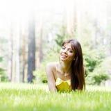 Ung kvinna i den gula klänningen som ligger på gräs Royaltyfri Foto