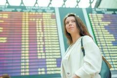 Ung kvinna i den internationella flygplatsen som ser informationsbrädet om flyg som kontrollerar för flyg Arkivfoto