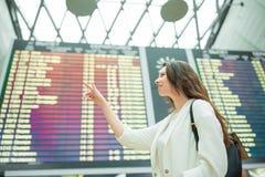 Ung kvinna i den internationella flygplatsen som ser informationsbrädet om flyg som kontrollerar för flyg Arkivfoton