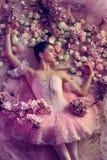 Ung kvinna i den rosa balettballerinakjolen som omges av blommor arkivbilder