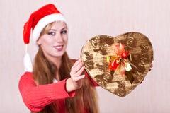Ung kvinna i den Santa Claus hatten med gåvaasken Royaltyfri Foto