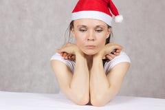 Ung kvinna i den Santas hatten Arkivbild