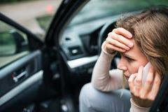 Ung kvinna i den skadade bilen efter en bilolycka som gör en påringning royaltyfria foton