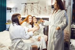 Ung kvinna i den vita badrocken med champagneexponeringsglas på ett brunnsortparti royaltyfria bilder