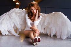 Ung kvinna i den vita bodysuiten med ängelvingar arkivfoto
