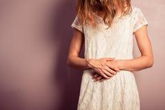 Ung kvinna i den vita klänningen med mageplågor Arkivbild