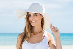 Ung kvinna i den vita solhatten som kopplar av på stranden Fotografering för Bildbyråer
