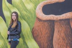 Ung kvinna i det stads- landskapet - grafitti royaltyfria bilder