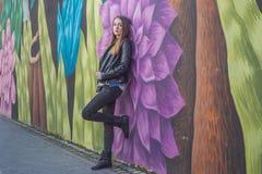 Ung kvinna i det stads- landskapet - grafitti arkivfoto