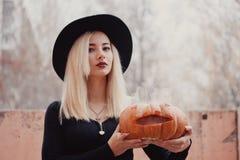 Ung kvinna i det svarta laget som rymmer den halloween pumpan med den vita röken som från inre kommer av den i hösten arkivfoton