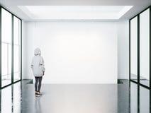 Ung kvinna i det tomma moderna gallerit som ser den tomma kanfasen Royaltyfria Bilder