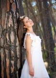 Ung kvinna i det vita klänninganseendet vid trädet i skog Royaltyfria Foton