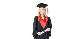 Ung kvinna, i diplom och att se för akademikermössa hållande bort Royaltyfri Bild