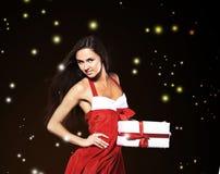 Ung kvinna i dräkt av Santa Claus med shopping på julbakgrunden Royaltyfri Bild