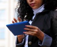 Ung kvinna i dräkt genom att använda en utomhus- minnestavla Royaltyfri Bild