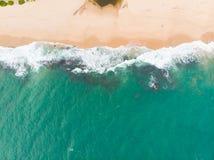 Ung kvinna i en bikini som ligger på baksidan på den vita sanden nära vågorna av det blåa havet Sri Lanka fotografering för bildbyråer