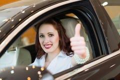 Ung kvinna i en bil och uppvisning tummar upp Arkivbild
