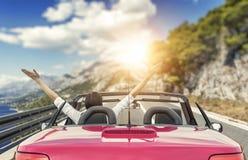 Ung kvinna i en bil på vägen till havet mot en bakgrund av härliga berg på en solig dag arkivbild