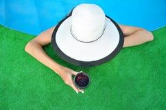 Ung kvinna i en hatt och ett exponeringsglas av rött vin Royaltyfria Bilder