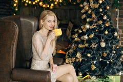 Ung kvinna i en hemtrevlig inre av jul En flicka sitter med en guling rånar under en julgran bland många gåvor Prepa arkivbild