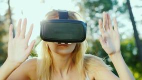 Ung kvinna i en hjälm av virtuell verklighet Rörande osynlig vägg Arkivfoto