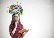 Ung kvinna i en klänning med en bok, hjärna, kugghjul Arkivfoton