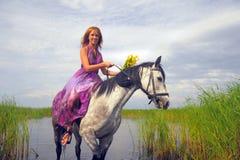 Ung kvinna i en klänning på en häst fotografering för bildbyråer