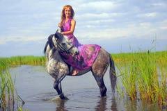 Ung kvinna i en klänning på en häst royaltyfria bilder