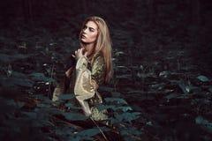 Ung kvinna i en mörk felik skog royaltyfria bilder