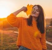Ung kvinna i en orange tröja med med gula sidor, utomhus- stående i mjukt soligt dagsljus Höst Solnedgång cozy royaltyfria foton