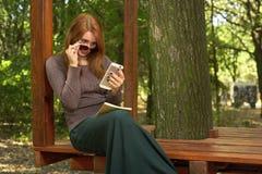 Ung kvinna i en parkera som läser ett meddelande Arkivbild