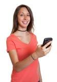Ung kvinna i en röd skjorta som skriver ett meddelande Arkivbild