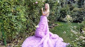 Ung kvinna i en rosa klänning med långt posera för drev stock video