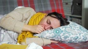 Ung kvinna i en säng med ett kallt arkivfilmer