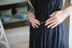 Ung kvinna i en svart aftonkl?nning royaltyfri bild