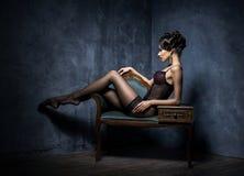 Ung kvinna i erotisk damunderkläder i en studio Arkivfoton