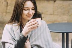 Ung kvinna i ett gatakafé som dricker kaffe arkivfoto